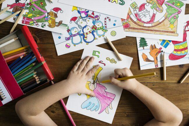 bambina che colora un disegno di Natale